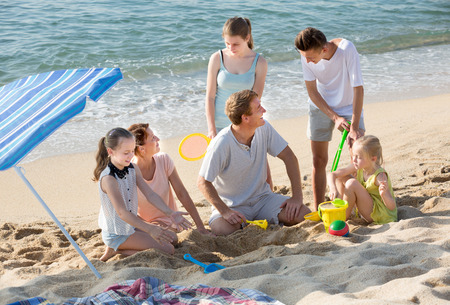 six people: Large carefree family of six people playing together with sand and active games on beach Stock Photo