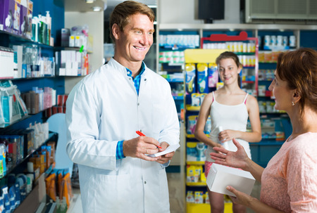 druggist: portrait of smiling russian man druggist in white coat giving advice to customers in pharmacy