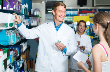 druggist: portrait of glad man druggist in white coat giving advice to customers in pharmacy