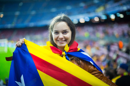 Excited positive adult girl with Catalonia flag rooting for football team Stock Photo