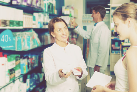 druggist: Portrait of cheerful woman druggist wearing white coat giving advice to customer in pharmacy Stock Photo