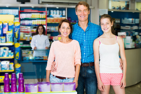 three persons: Positive family of three persons standing in pharmacy among shelves with goods