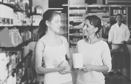 shopping questions: Portrait of attractive woman with daughter teenager shopping healthcare products in drug store Stock Photo