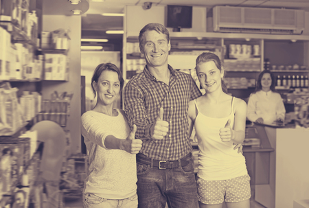 three persons: Laughing family of three persons holding thumbs up in pharmacy among shelves with goods