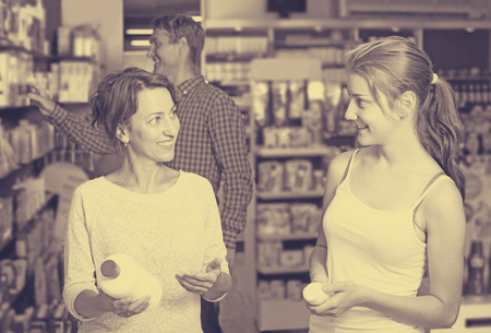 buying questions: Portrait smiling woman with young daughter shopping healthcare products in drug store Stock Photo