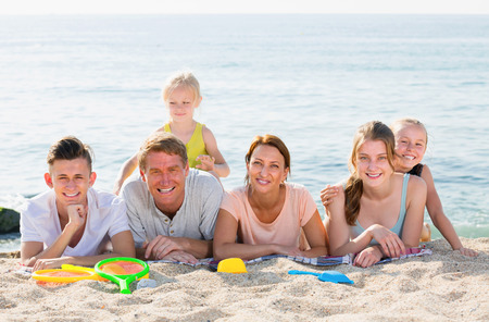 large: Large family of six people happily lying together on beach on clear summer day Stock Photo