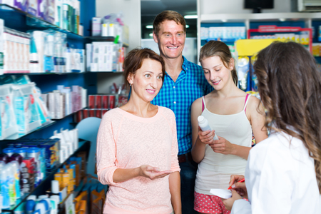 druggist: Cheerful family of three persons consulting druggist in pharmacy. Focus on mature woman