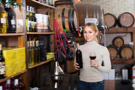 food shop: Young glad female customer taking bottle of wine in food shop