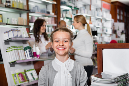 article of clothing: Little  girl holding a product box in the pharmacy with parents and pharmacist on the background