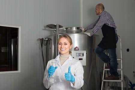 production facility: Portrait of adult girl employee in modern beer production facility