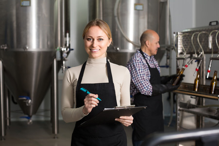 technologist: Portrait of joyful young female technologist on beer brewery factory