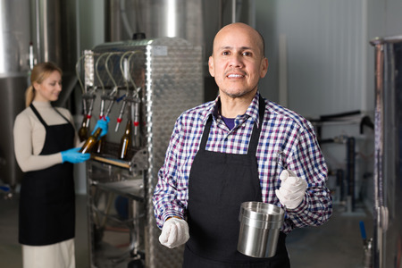 production facility: Positive  smiling mature man working on modern beer production facility