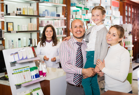 three persons: Cheerful smiling family of three persons getting help of a pharmacist in the pharmacy Stock Photo