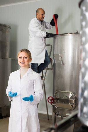 production facility: Portrait of laughing woman employee in modern beer production facility