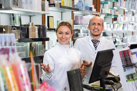 diligente: Two friendly diligent female and male pharmacists in white coats working the pharmaceutical store