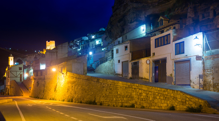 Street at town with dwelling  houses into rock in evening. Alcala del Jucar.    Castile-La Mancha,  Spain Stock Photo