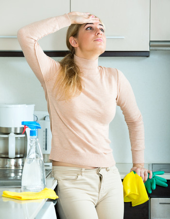 Unhappy adult woman in rubber gloves posing at kitchen