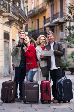 sights: Portrait of  happy spanish tourists with map and baggage seeing the sights in European city Stock Photo