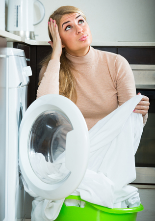 quality home: Housewife displeased with washing quality of linen after laundry at home Stock Photo