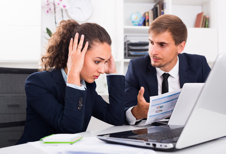 solve problems: portrait of depressed business man and woman colleagues trying to solve problems in office