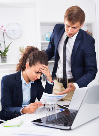 Sad subordinate woman being accused to making mistake by man colleague in company office Stock Photo