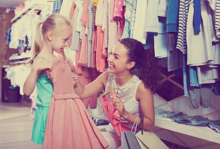 color in: Brunette feliz joven madre con su hija la compra de ropa de niños de color rosa en la tienda