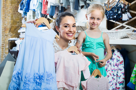 interested: young interested mother with daughter buying kids clothes in shop Stock Photo