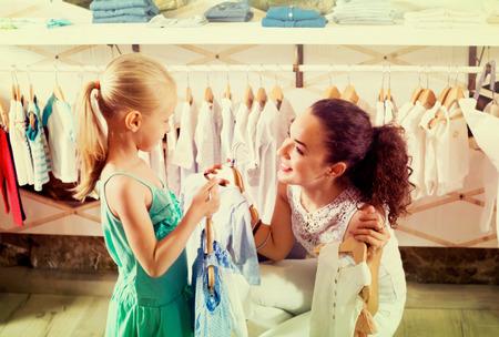 ff5ef8dd7fe #61470666 - Feliz mujer joven y sonriente con la pequeña hija selección de azul  ropa de los niños en tienda de ropa