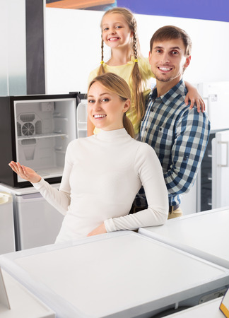 selecting: Portrait of smiling family selecting refrigerator in appliance store