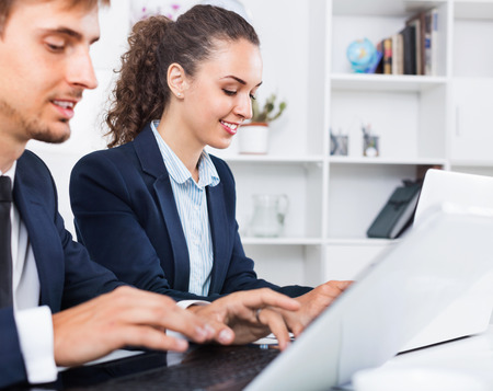 glad: Glad business female assistant wearing formalwear using laptop in company office Stock Photo