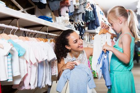 ea31fe06301 #61470685 - Madre con la hija de comprar ropa de niños en color azul en la  tienda