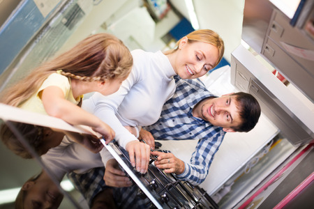 Smiling parents with daughter choosing kitchen range at the home appliance store. Focus on woman Stock Photo