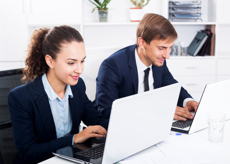 Man and young woman coworkers sitting and working on computers in firm office. Focus on the woman