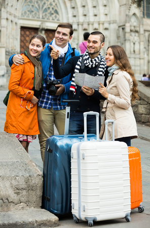 group direction: Group of happy friends with luggage checking direction in map outdoor