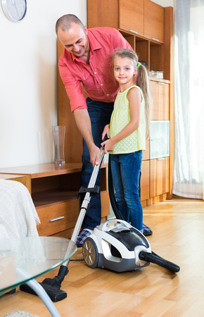 5s: Happy dad and his little daughter hoovering apartment together