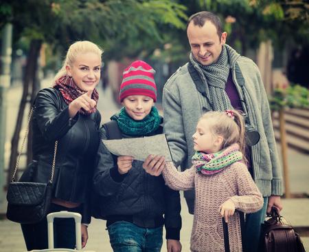 clase media: familia de clase media de cuatro miembros feliz comprobar una dirección en un mapa