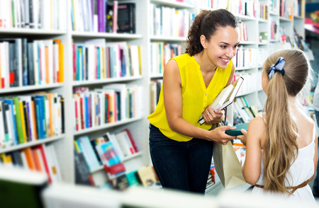 Young positive woman giving book to girl in school age in bookstore