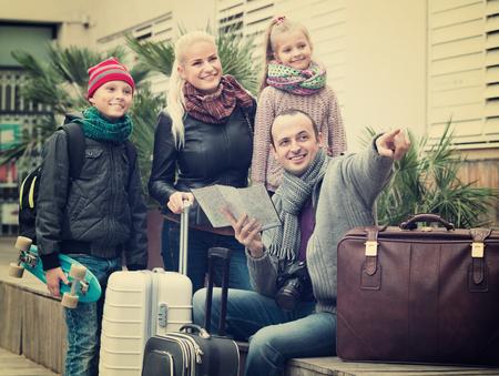 clase media: familia de clase media de cuatro miembros feliz comprobar una dirección en el mapa al aire libre