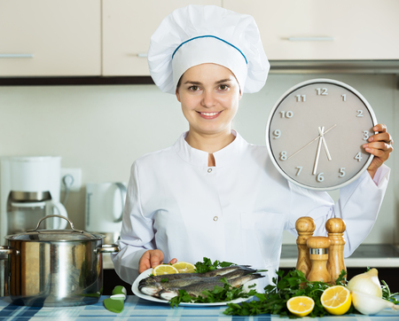 ready to cook food: Positive woman in cook uniform waiting food to be ready with clock in hands Stock Photo