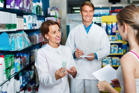 white coats: Smiling efficient male and female pharmacists wearing white coats working in drug store