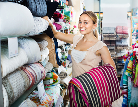 bedspread: Young happy smiling  woman buying bed spread in home textile store