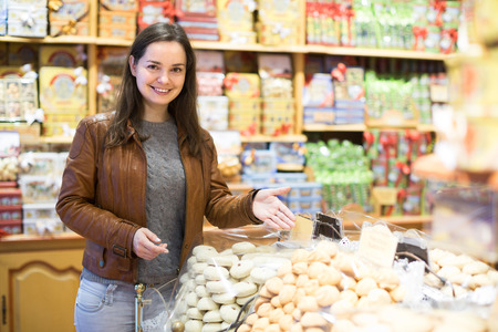 pastila: Portrait of happy smiling young woman shopping in candy store Stock Photo