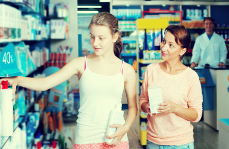 Portrait of happy woman with daughter teenager shopping healthcare products in drug store