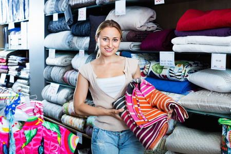 Smiling glad woman buying bed spread in home textile store Stock Photo
