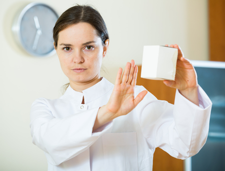 Professional female doctor warning of useless dietary supplement Stock Photo