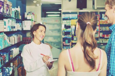 diligent: Diligente amigable farmacéutico de sexo femenino con uniforme de trabajo en la tienda de productos farmacéuticos Foto de archivo