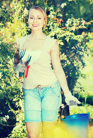 horticultural: Glad smiling young  woman having horticultural instruments in garden on summer day