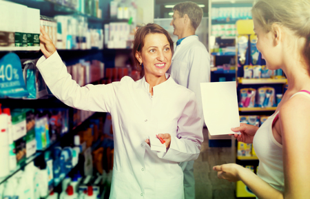 druggist: Portrait of happy woman druggist wearing white coat giving advice to customer in pharmacy Stock Photo