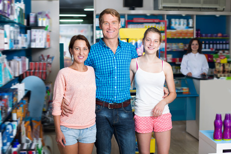 three persons: Happy family of three persons standing in pharmacy among shelves with goods Stock Photo