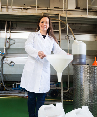 extracting: Brunette woman with plastic bottles in oil extracting section Stock Photo